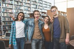 Positive students situating in athenaeum royalty free stock image