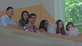 Positive students studying during the lesson. Positive students studying during lesson in the university classroom with modern desing and big, spacy panoramic stock footage