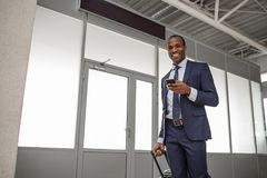 Positive stylish african man is surfing internet using smartphone stock image