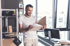 Positive stylish mature man is standing with smile. Checking papers. Happy adult bearded employee is leaning on shelf in cozy office with smile. He is looking at Stock Photo