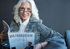 Positive stylish old woman is enjoying periodical in office. Business news. Portrait of optimistic charming gray-haired senior lady in glasses is sitting on sofa Royalty Free Stock Image