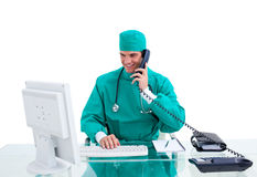 Positive surgeon on phone working at a computer Stock Photos