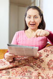 Positive surprised mature woman looks newspaper Stock Photos