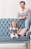 Positive sweet girl sitting near the cushion Stock Images