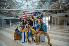 Positive team are feeling gladness while waiting for flight. Real patriots. Full length portrait of joyful young friends are posing at airport lounge with usa stock images
