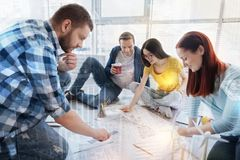 Positive team working at one project. Work in-group. Enigmatical female sitting in semi position and bowing head while looking at sketch Stock Image