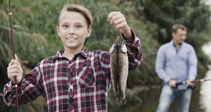 Positive teenage boy releasing catch on hook fish Stock Photos