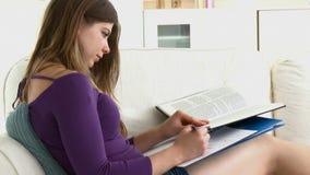 Positive teenager doing homework on the sofa stock footage