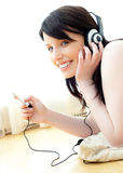 Positive teenager listening to music on the floor Royalty Free Stock Photos