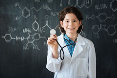 Positive teenager using stethoscope at school. Making important choise. Delightful smiling skilled teenager standing near the blackboard at school while enjoying Stock Photography