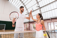Positive tennis players giving high five. Thank you for set. Positive professioanl tennis players standing near net and giving high five while resting after Stock Photo