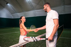 Positive tennis players shaking hands. Lets start.Cheerful professional tennis players standing near net and shaking hands while going to play tennis Stock Images