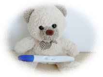 Positive Test. Teddy bear holding a positive pregnancy test Stock Photo