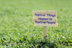 Positive things happen to positive people. Wooden sign in grass,blur background Stock Photos