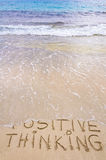 Positive Thinking message written on sand, with waves in background Stock Images