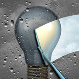 Positive Thinking. And negative outlook as a wiper clearing a cloudy wet window with a grey dark light bulb and a wiper cleaning it to expose a clean bright Stock Photos