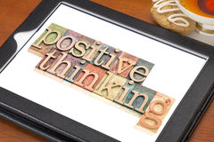 Positive thinking typography on tablet. Positive thinking typography - isolated text in letterpress wood type blocks on a digital tablet with a cup of tea royalty free stock photos