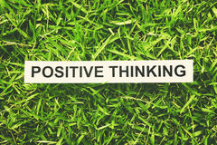 Positive thinking. Word positive thinking paper on green grass (retro style Royalty Free Stock Photography