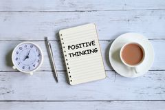 Positive thinking written on notebook. Top view of table notebook written with `THINKING POSITIVE` with table clock,pen and a cup of coffee on white wooden Royalty Free Stock Photography