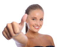 Positive thumbs up success for happy young girl. Thumbs up hand sign for positive success by a beautiful happy young teenager girl with big cheerful smile and Royalty Free Stock Photography