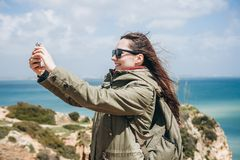 A positive tourist girl takes a beautiful view or does a selfie or communicates with someone online using a cell phone stock photo