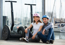 Positive tourists couple relaxing near segways Royalty Free Stock Photos