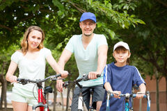 Positive tourists with son riding bicycles in park Royalty Free Stock Photography