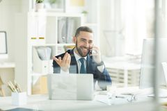 Positive trader consoling customer about financial assets. Positive confident young bearded trader in formal suit sitting at table and gesturing hand while royalty free stock photo