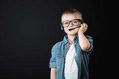 Positive tragende Kopfhörer des kleinen Jungen mit Mikrofon Stockfotos