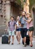 Positive travelers walking the street Stock Photo