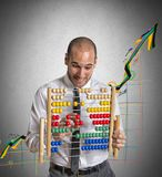 Positive trend. Businessman with abacus calculates a positive trend Royalty Free Stock Photo
