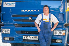 Positive truck driver stands near his lorry Stock Photos