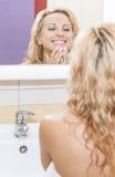 Positive und sinnliche kaukasische blonde Frau, die im Spiegel schaut und ihr Gesicht überprüft Stockfoto