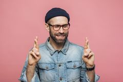 Positive unshaven male with glad look crosses fingers, keeps eye stock photography