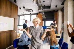 Positive Unternehmensfrau mit dem kurzen blonden Haar, das stilvolles Kleid trägt Lizenzfreie Stockbilder