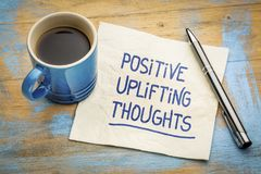 Positive, uplifting thoughts. Handwriting on a napkin with a cup of espresso coffee royalty free stock photos