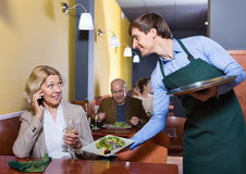 Positive waiter bringing order to happy charming mature female Royalty Free Stock Photos