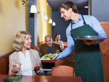 Positive waiter bringing order to mature female Royalty Free Stock Images