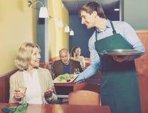 Positive waiter bringing order to mature female Stock Images