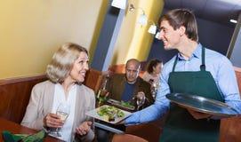 Positive waiter bringing order to smiling mature female Stock Photo