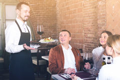 Positive waiter placing order in front of guests. In country restaurant Stock Images