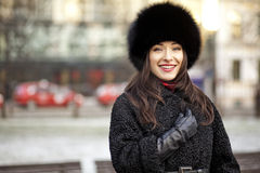 Positive winter girl. Winter girl wearing fur hat, coat and gloves in park Stock Photos