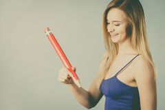 Positive woman holds big pencil in hand Royalty Free Stock Photos