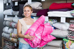 Positive woman choosing blanket. In bedding section in shop Stock Photos