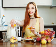 Positive woman cooking  beverages  from peaches Stock Images