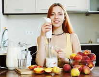 Positive woman cooking dairy beverages Stock Photos