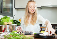 Positive woman cooking fish in flour Royalty Free Stock Images