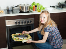 Positive woman cooking  fish in oven at  kitchen Stock Image