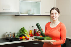 Positive woman cooking with  vegetable marrow Stock Photo