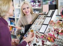 Positive  woman customer chooses cosmetics. Positive women customer chooses cosmetics in store Royalty Free Stock Photos